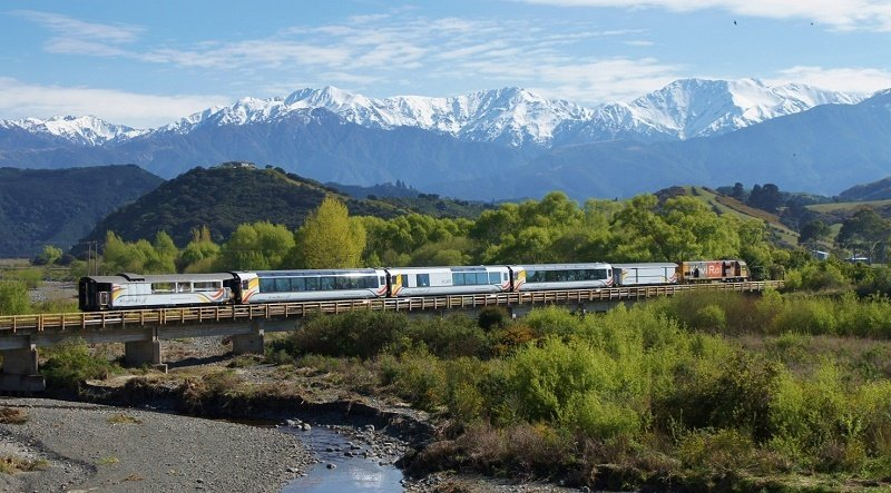 Rail New Zealand. På 4,5 timer farer toget over Canterbury-slettene, langs Waimakariri-elven via Arthur-passet.